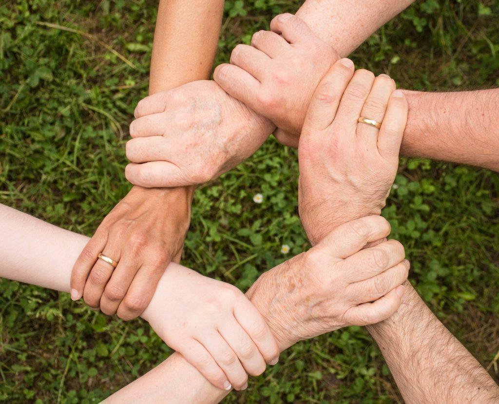 Bildet viser ulike hender som former en ring.