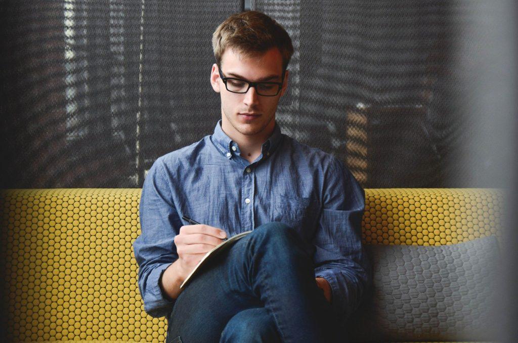 Ung mann som sitter i en sofa og noterer i en bok.