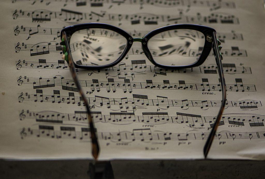 Briller som ligger på et noteark. Uklart bilde.
