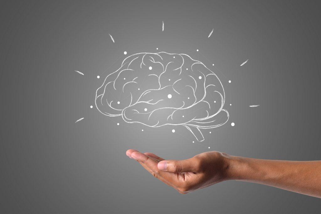 Hånd som holder en hjerne.