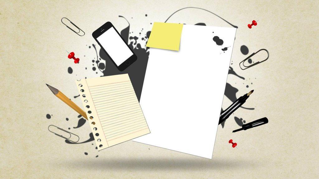 Smarttelefon og skrivesaker.