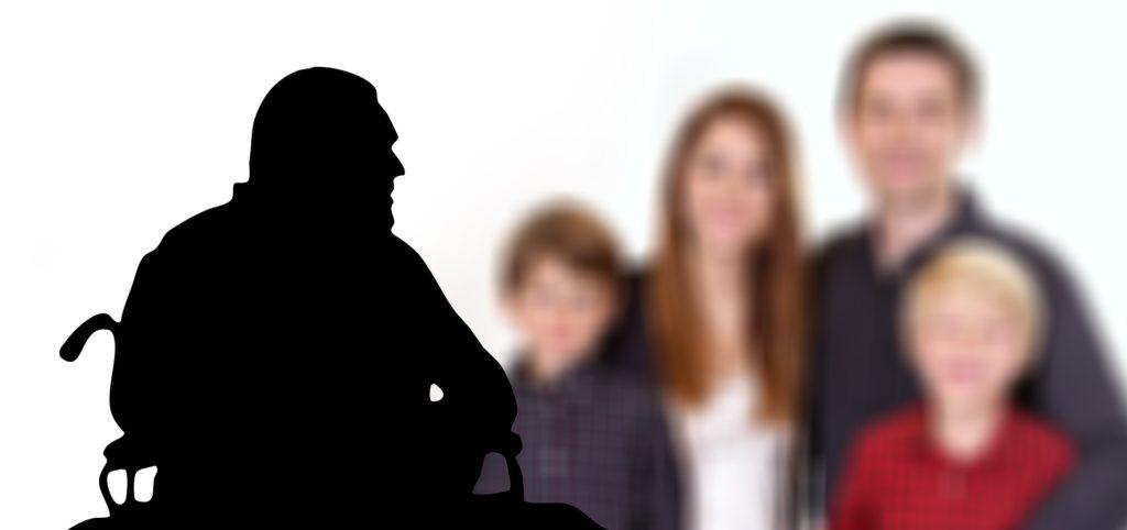Mann som sitter i rullestol, uklare mennesker står i bakgrunnen.