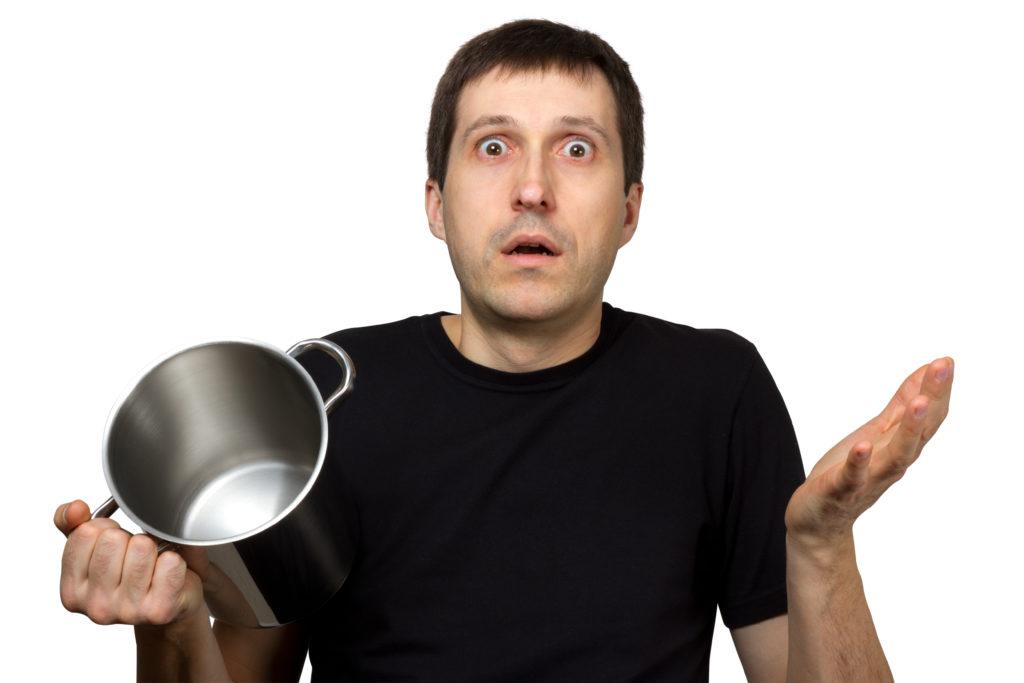 Mann som holder en kasserolle og ser forvirret ut.