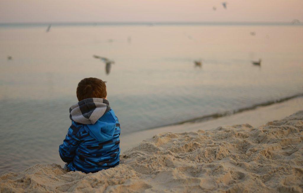 Gutt som sitter alene på stranden og ser ut over havet.