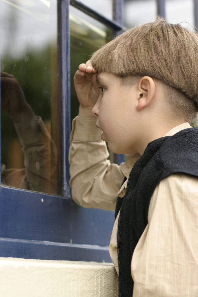 Et barn som ser inn gjennom et vindu.