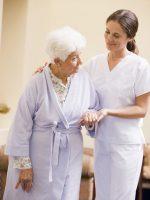 Sykepleier som støtter eldre dame på venstre side.